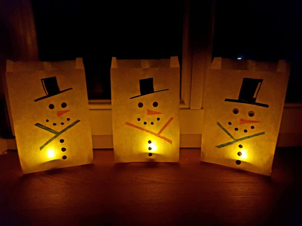 snowman luminaries at night